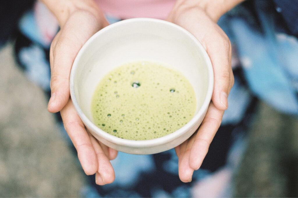 haende halten eine tasse gruenen tee
